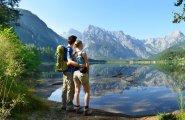 © Röbl  | Wanderer am Almsee: Pärchen legt auf einer Wandertour einen Zwischenstopp ein und blickt über den Almsee auf das Tote Gebirge.